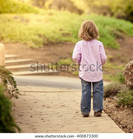 Boy standing across the road. - stock photo