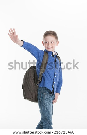 boy standing and waving hand on white. cute school boy holding hands in pocket - stock photo