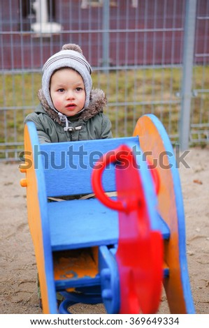 Boy standing by a wooden spring on a play ground