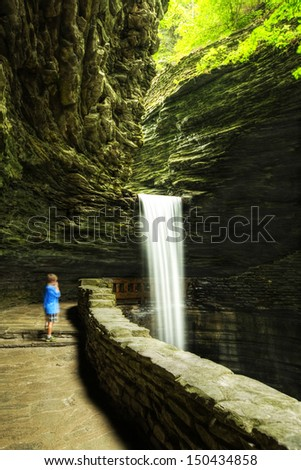Boy standing by Waterfalls at Watkins Glen (long exposure photography) - stock photo