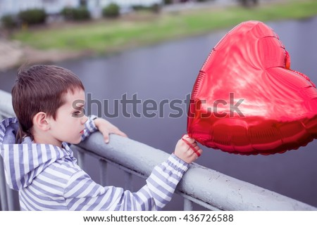 boy standing on the bridge and holding a red heart. the concept of lost love. sad child with a balloon in the form of heart looking at the river from the bridge - stock photo
