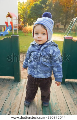 Boy standing on wooden platform at a play ground - stock photo