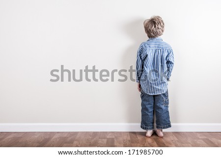 Boy standing up against a wall - stock photo