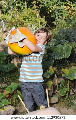 boy standing with big yellow pumpkin in hands
