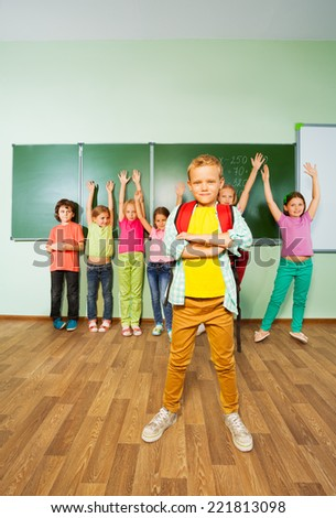 Boy stands in front of children with hands up - stock photo