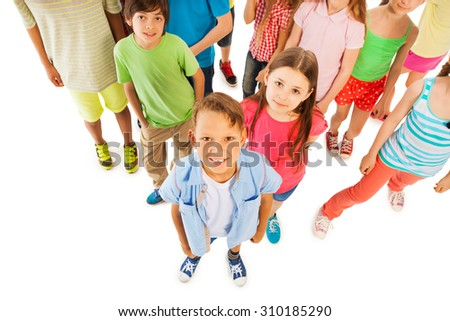 Boy stands in front of large kids group from above