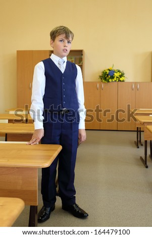 Boy stands next to desk in classroom and answer teacher question in school. - stock photo