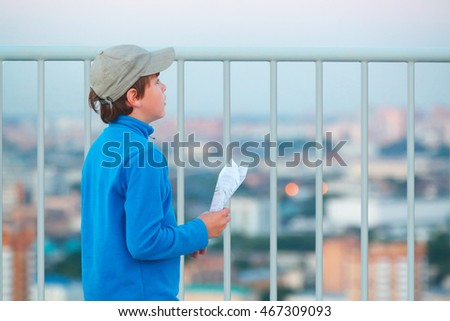 Boy stands on roof of multistory building with paper airplane in hands