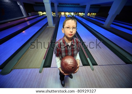 Boy stands with  ball for bowling and looks ahead - stock photo