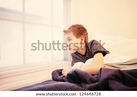 Boy staring out the window on a winter morning - stock photo