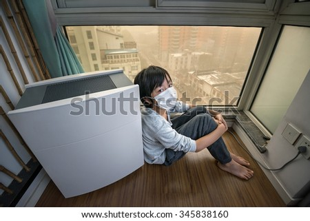 Boy staying home near air purifier on extremely polluted day