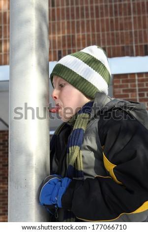 Boy sticking his tongue on a flag pole - stock photo