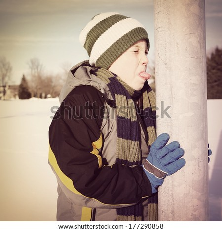Boy sticking his tongue on a metal pole - stock photo
