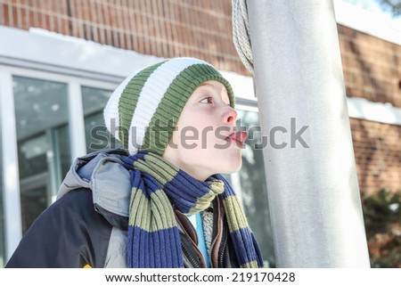 Boy sticking his tongue to a flag pole - stock photo