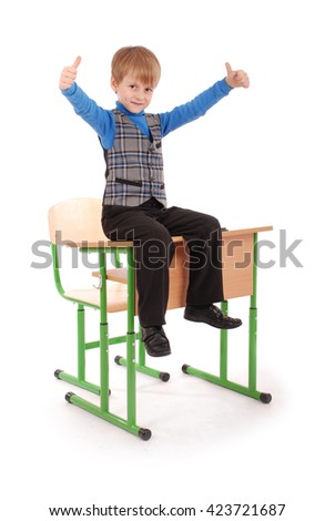 Boy Success. Boy sitting on the school desk isolated on white