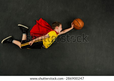 Boy superhero with a basketball
