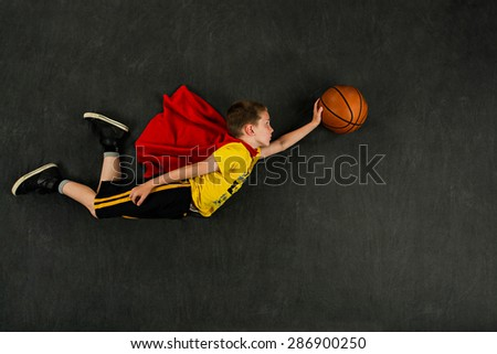 Boy superhero with a basketball - stock photo