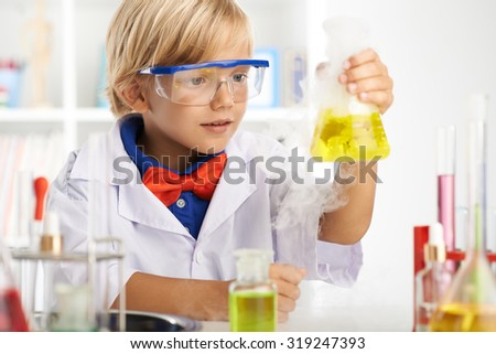 Boy surprisingly looking at flask with fuming acid
