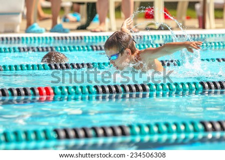 Boy swimming Butterfly in a race. Focus on face and water drops, some motion blur.