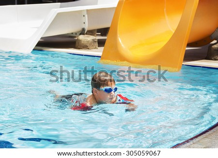 Boy swimming in pool wearing glasses and inflatable over-sleeves with toy water gun outdoors. Water slides