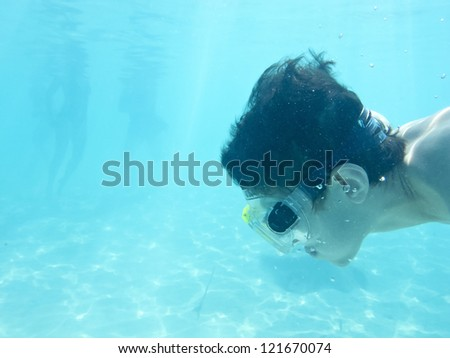 boy swimming underwater in the ocean, room for text in water area - stock photo