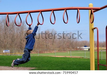 Boy Swings across playground equipment - stock photo