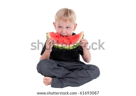 Boy taking a bite from a juicy watermelon - stock photo