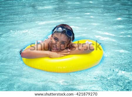 boy taking sunbath in pool on rubber ring, retro toned - stock photo