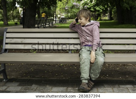 Boy talking on the mobile phone in the park - stock photo
