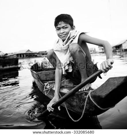 Boy Taveling Boat Floating Village Cambodian Vessel Concept - stock photo