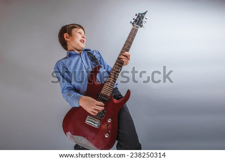 boy teenager European appearance brown emotionally plays guitar - stock photo