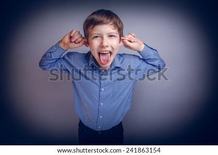 boy teenager European appearance brown grimaces experiencing joy cross process - stock photo