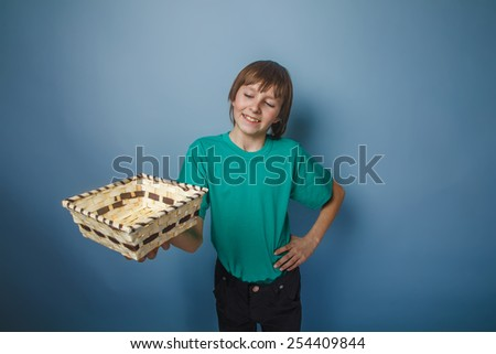 boy teenager European appearance brown hair in a shirt holding a wicker box outstretched hands on a gray background, smiling - stock photo