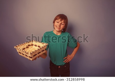 boy teenager European appearance brown hair in a shirt holding a wicker box outstretched hands on a gray background, smiling retro