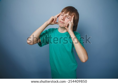 boy teenager European appearance brown hair in a turquoise t-shirt pressed his fingers to his temple on a gray background, thinking, thought head pain - stock photo