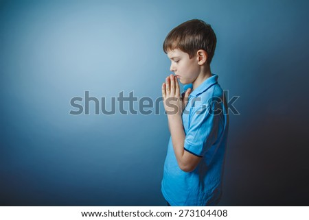 boy teenager European appearance in a blue shirt brown hair hung his head on a gray background, prayer - stock photo