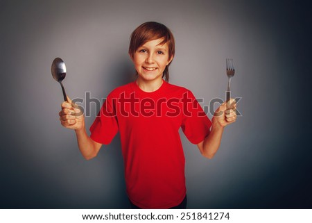boy teenager European appearance in a red shirt holding a spoon and a fork on a gray background retro