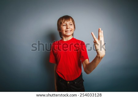 boy teenager European appearance in a red shirt showing thumbs digit three on a gray background, the score cross process - stock photo