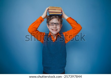 boy teenager European appearance in brown hair retro dress with glasses put the book on his head on a gray background, smile - stock photo