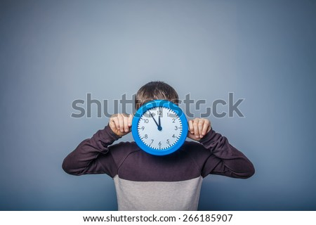 boy teenager European appearance in brown sweater covered his face with a clock on gray background, time