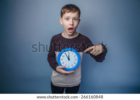 boy teenager European appearance in brown sweater holding a blue clock showing thumbs up on an arrow during five minutes to twelve on a gray background, watch, wonder - stock photo