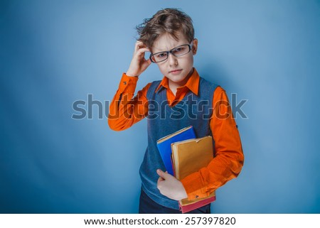 boy teenager European appearance in retro clothes with books in glasses thoughtfully scratching his head on a gray background, thoughts - stock photo