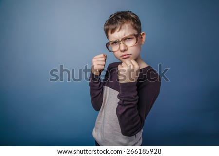 boy teenager European appearance in sunglasses in brown hair jacket clenched his hands into fists frowned on gray background, fight, protection - stock photo