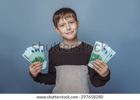Boy teenager European appearance ten years holding a wad of money on a  gray background - stock photo