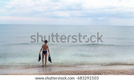 Boy teenager in swimming trunks and underwater mask carries flippers going to calm sea
