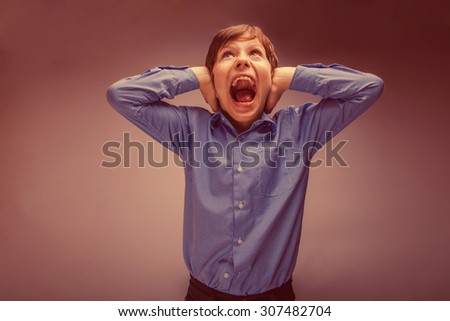boy teenager of European appearance brown hair closed his ears shouting on gray background retro - stock photo