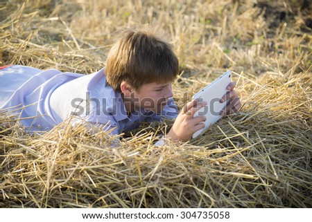 Boy teenager playing on a tablet in the field - stock photo