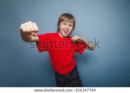Boy, teenager, twelve his  red  in shirt, fists  red showing   years - stock photo