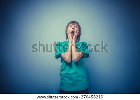 boy, teenager, twelve years a  in green shirt, opened his mouth, surprised instagram effect style - stock photo