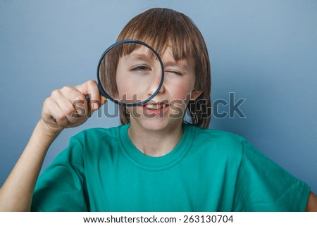 Boy, teenager, twelve years in a green t-shirt, looking through a magnifying glass with one eye - stock photo